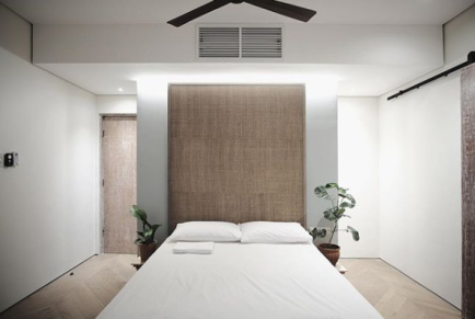 4 engineered wood flors and a natural fiber headboard provide this ecohouse master bedroom with a relaxing mood